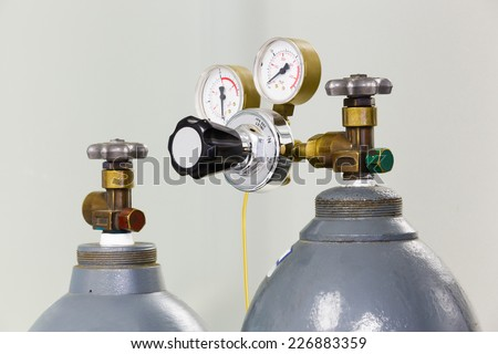 Close up gauges and valve on old nitrogen gas cylinder in laboratory - stock photo