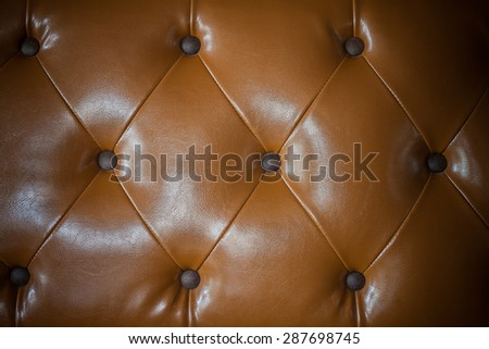 Close up genuine leather upholstery background for a luxury decoration in Brown tones - stock photo