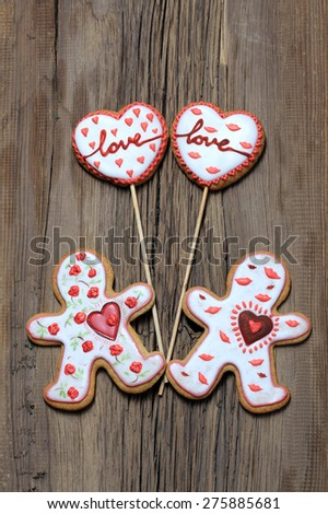 close-up ginger biscuits in the shape of hearts and men on the background of an old tree - stock photo