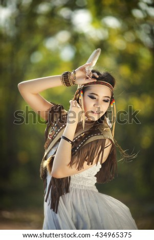 Close-up girl archer with traditional costume suit and fur hat. Summer forest on the background. - stock photo