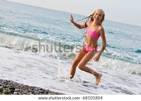 Close-up girl running from sea wave