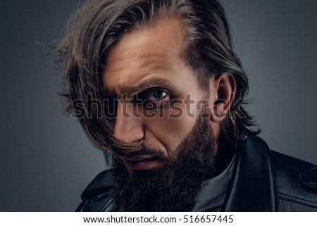Close up glance studio portrait of bearded  male with a wild look.
