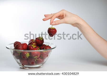 Close-up. Glass Bowl Of Strawberries. Fresh strawberries in hands on white background. Woman putting strawberries on plate. Large transparent glass salad bowl full of ripe strawberries. - stock photo