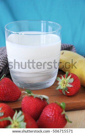 Close up glass of fresh milk with strawberries and banana