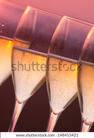 Close up glasses of champagne with sunset background - stock photo