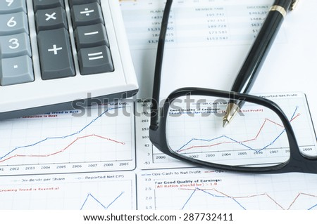 Close up glasses ,pen and calculator on business graph