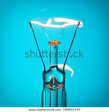 Close up glowing light bulb on blue - stock photo