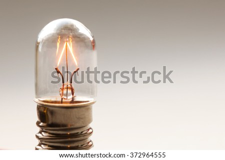 Close up glowing light bulb, Retro style filament lamp macro view. Warm colors background. Soft focus. Copy space - stock photo