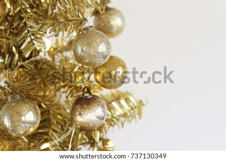 close up gold christmas tree with white lights and vintage silver and gold ornaments white