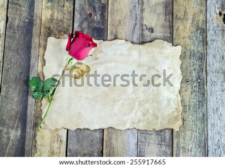 Close up gold ring, red rose and old paper on wooden background