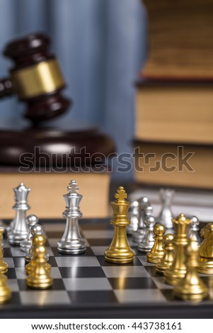 Close up golden check on lawyer working desk with wooden gavel and law book as blurry background. - stock photo