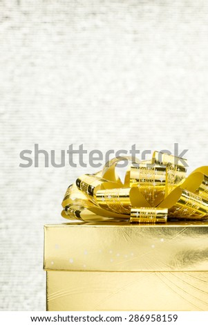 Close up Golden present box with big bow at bokeh white blur background, Leave space on to adding your content