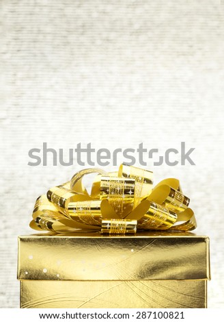 Close up Golden present box with big bow at bokeh white blur background, Leave space on top to adding your content - stock photo