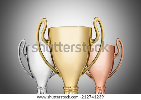 Close up golden,silver and bronze trophies on gray background - stock photo