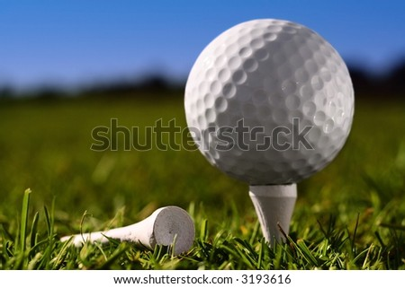 Close up golf ball on peg. Shallow depth of field with focus on front of ball and peg on ground. - stock photo