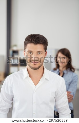 Close up Good Looking Young Businessman Inside the Office, Smiling at the Camera with his Female Co-Worker Behind Him. - stock photo