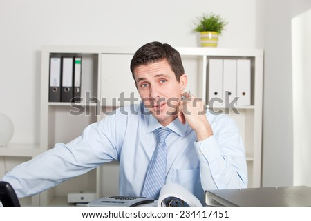 Close up gorgeous businessman in white long sleeve shirt and tie, sitting at his worktable, with documents and calculator, while touching his neck and looking at the camera - stock photo