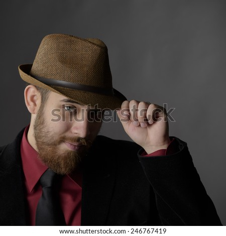 Close up Gorgeous Goatee Young Man Wearing Formal Wear While Holding his Brown Hat, Looking at the Camera. Isolated on Gray Background - stock photo