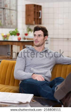Close up Gorgeous White Man Sitting on Couch at the Living Room Wearing Gray Long Sleeve Tops and Blue Jeans Outfit, Looking at his Right Angle. - stock photo