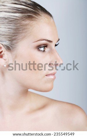 Close up Gorgeous Young Bare Woman with Blond Hair Looking at the Right Frame. Isolated on Gray Background. - stock photo