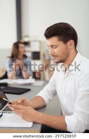 Close up Gorgeous Young Businessman Busy with his Mobile Phone, Sitting at his Table Inside the Office. - stock photo