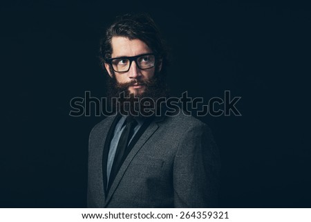 Close up Gorgeous Young Man with Long Goatee Beard, Wearing Formal Fashion with Eyeglasses, Looking to the Upper Right of the Frame on a Black Background.