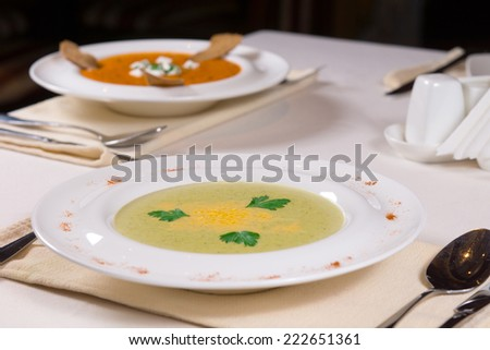 Close up Gourmet Appetizing Creamy Soup Dish on Shallow Bowl Served on White Table with Utensils on Sides. - stock photo