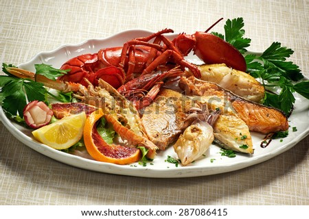 Close up Gourmet Appetizing Mixed Grilled Fish and Lobster Recipe Served on White Plate with Cilantro Herbs Placed on the Table. - stock photo
