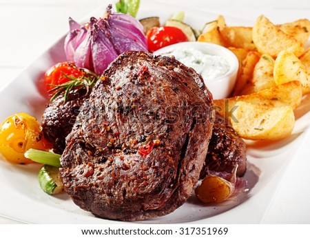 Close up Gourmet Appetizing Pepper Crusted Beef Steak with Potato Wedges and Dipping Sauce on White Plate - stock photo