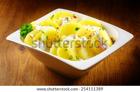 Close up Gourmet Boiled german Potato salad with Herbs and Spices on White Bowl Placed on Wooden Table. - stock photo