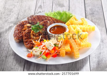 Close up Gourmet Fried Meat Slices with Potato Fries and Sauces on White Plate, Served on Wooden Table. - stock photo