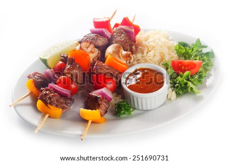 Close up Gourmet Main Dish of Kebabs on White Plate with Rice, Tomato Sauce and Fresh Veggies. Isolated on White Background. - stock photo