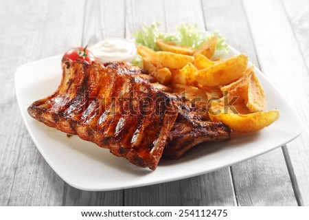 Close up Gourmet Main Dish with Grilled Pork Rib and Fried Potatoes on White Plate. Served on Wooden Table. - stock photo