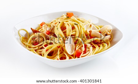 Close up Gourmet Tasty Paella Pasta Dish with Shells on a White Plate Served on the Table. - stock photo