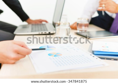 close-up graph and charts on the table during business meeting at office. Officer reports about financial achievements for a seminar