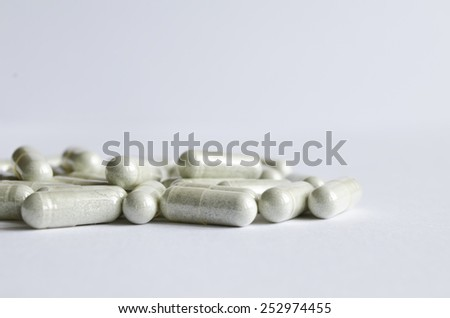 Close-up gray capsules on a white background. - stock photo