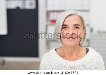 Close up Gray Haired Middle Aged Woman Smiling at the Camera Inside the Office. - stock photo
