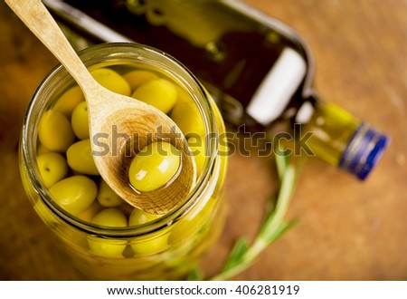 Close up green olives in bank, bottle of olive oil, rosemary on a wooden background