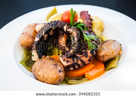 close-up grilled octopus tentacle served with stewed vegetables