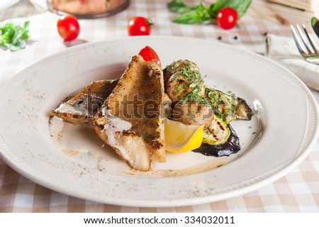 Close up grilling Fish fillet with vegetables - mushrooms, cabbage, eggplant, tomato and cream sauce decorated with lemon slice and greens on the white plate on the table with ingredients - stock photo