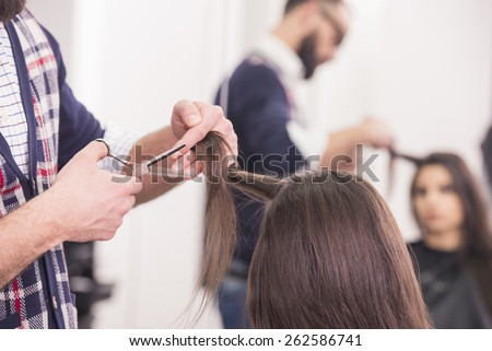 Close-up hairdresser cutting hair a woman in hairdresser salon. - stock photo
