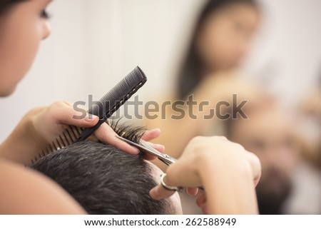 Close-up hairdresser with scissors and comb. Blurred background. - stock photo
