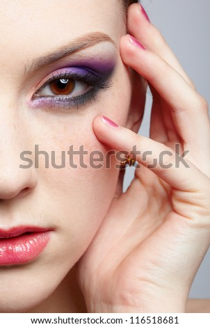 close-up half-face portrait of young beautiful woman touching her face with manicured hand - stock photo