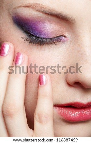 close-up half-face portrait of young beautiful woman with violet eye shadow