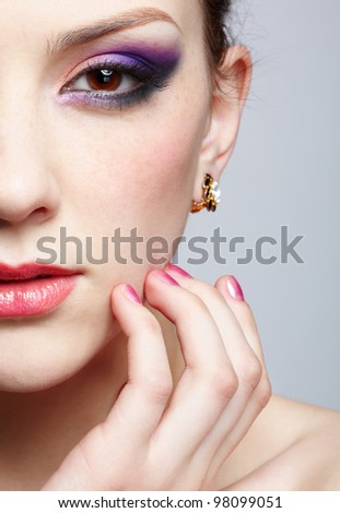 close-up half-face portrait of young beautiful woman with violet eye shadow touching her face with manicured fingers - stock photo