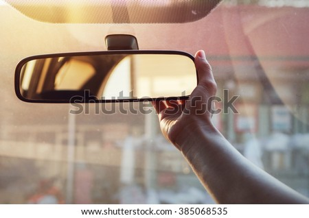 Close up Hand adjusting rear view mirror. - stock photo