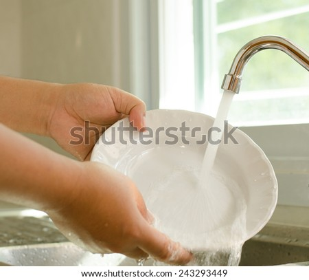 Close up Hand cleaning dish in kitchen room - stock photo