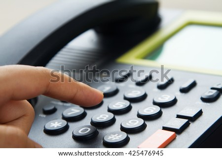 Close up hand dialing telephone, office of call center service for customer concept. - stock photo