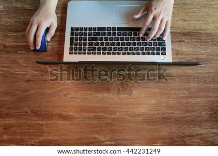 close up hand finger type laptop keyboard,  Hands multitasking working on laptop connecting internet and sitting at wooden table. management concept for achievement business strategy   - stock photo