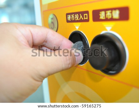 Close-up Hand holding a coin input self service machine - stock photo